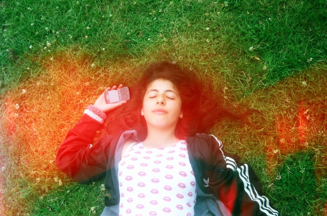 rally lying down on teh grass listening to music in the park
